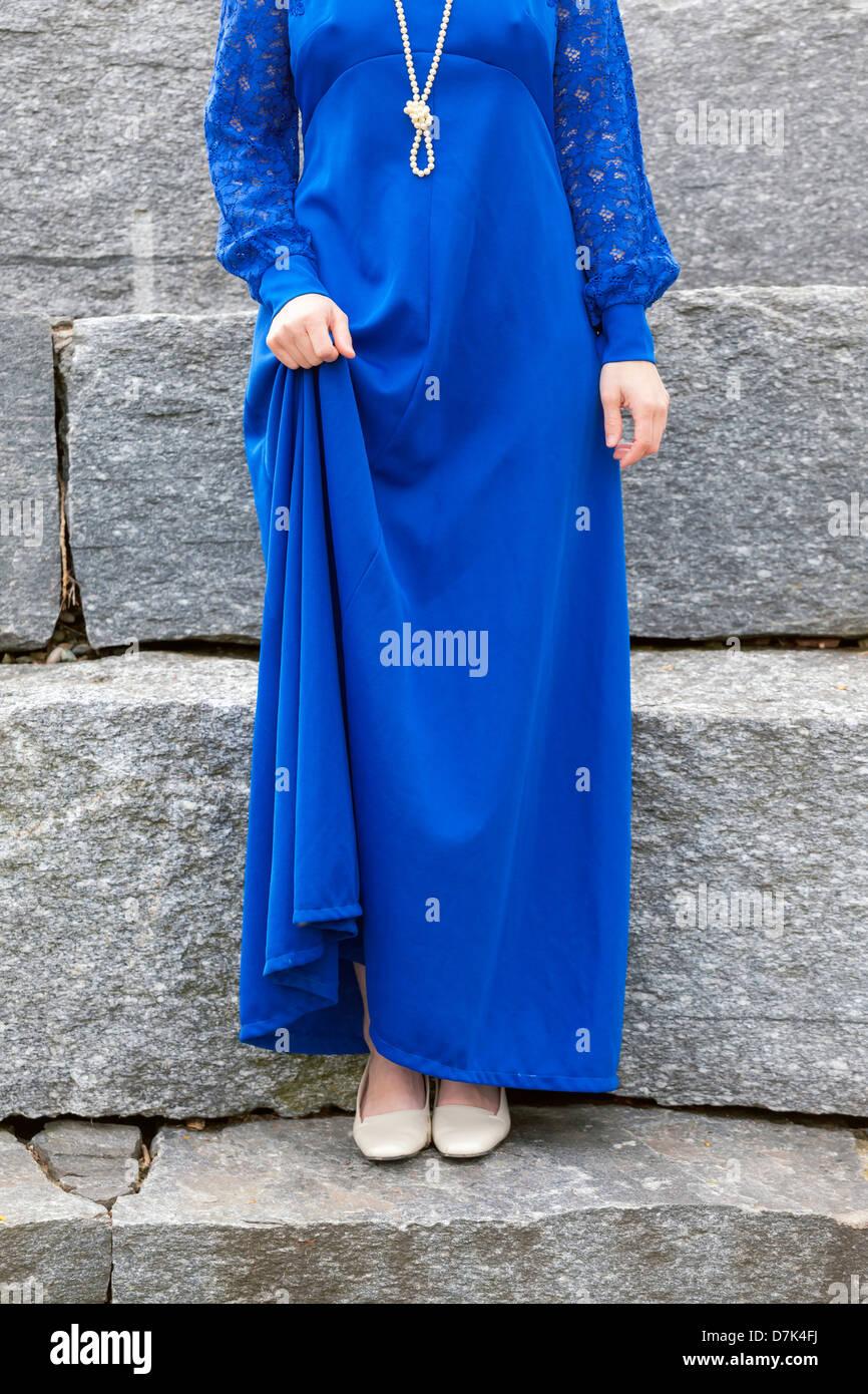 Una donna in un vestito blu è in piedi sui gradini di pietra Immagini Stock