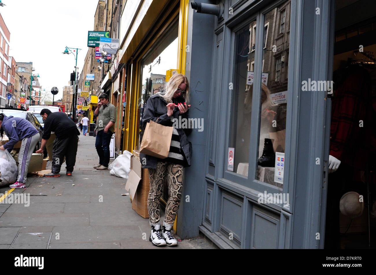 Una ragazza con il chiodo rosso utilizza un telefono in Brick Lane, London, Regno Unito Immagini Stock