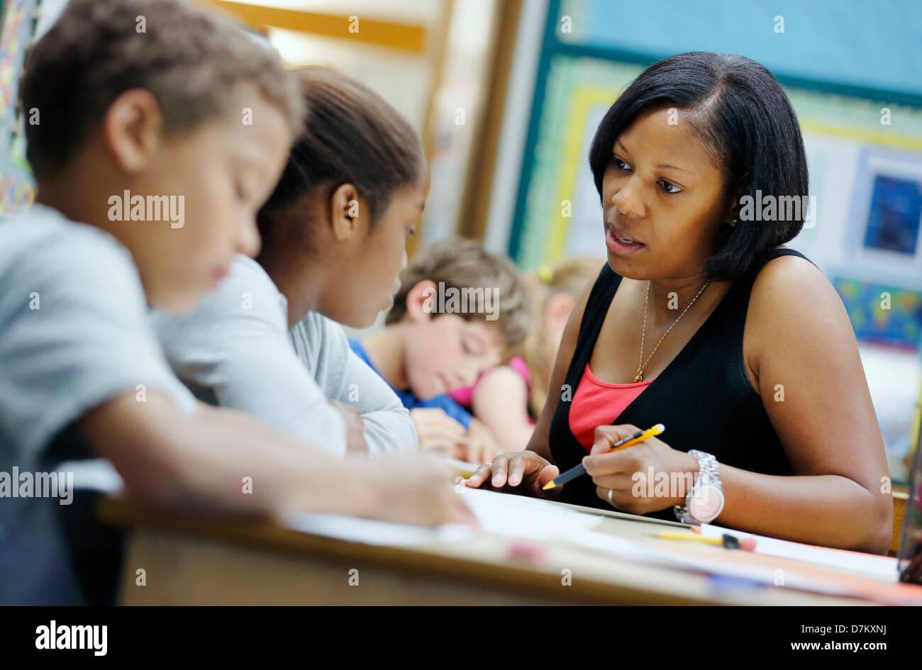 Insegnante di scuola elementare con gli studenti Immagini Stock