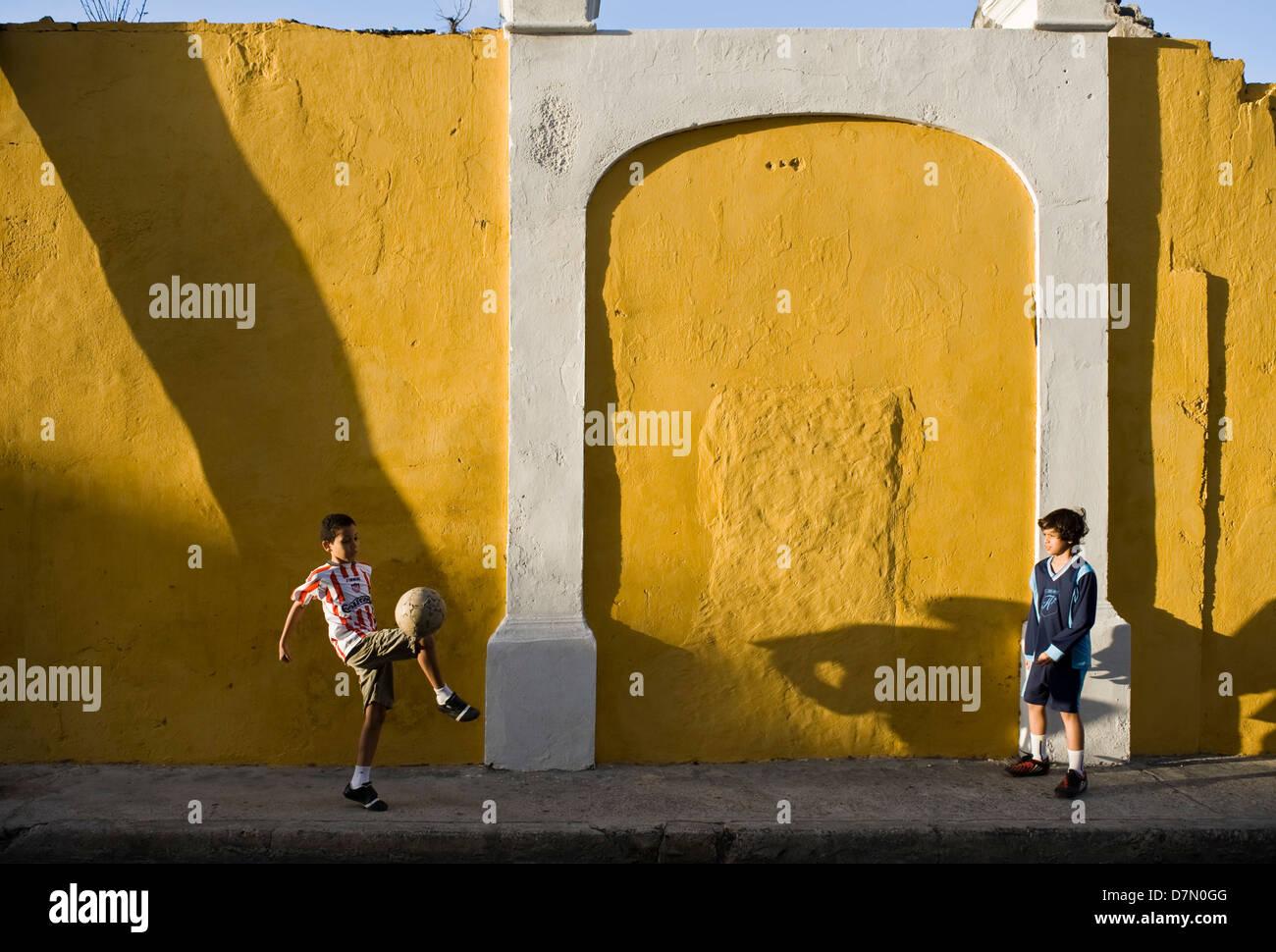 I ragazzi a giocare il gioco del calcio (soccer) nella città vecchia, Cartagena, Colombia Immagini Stock