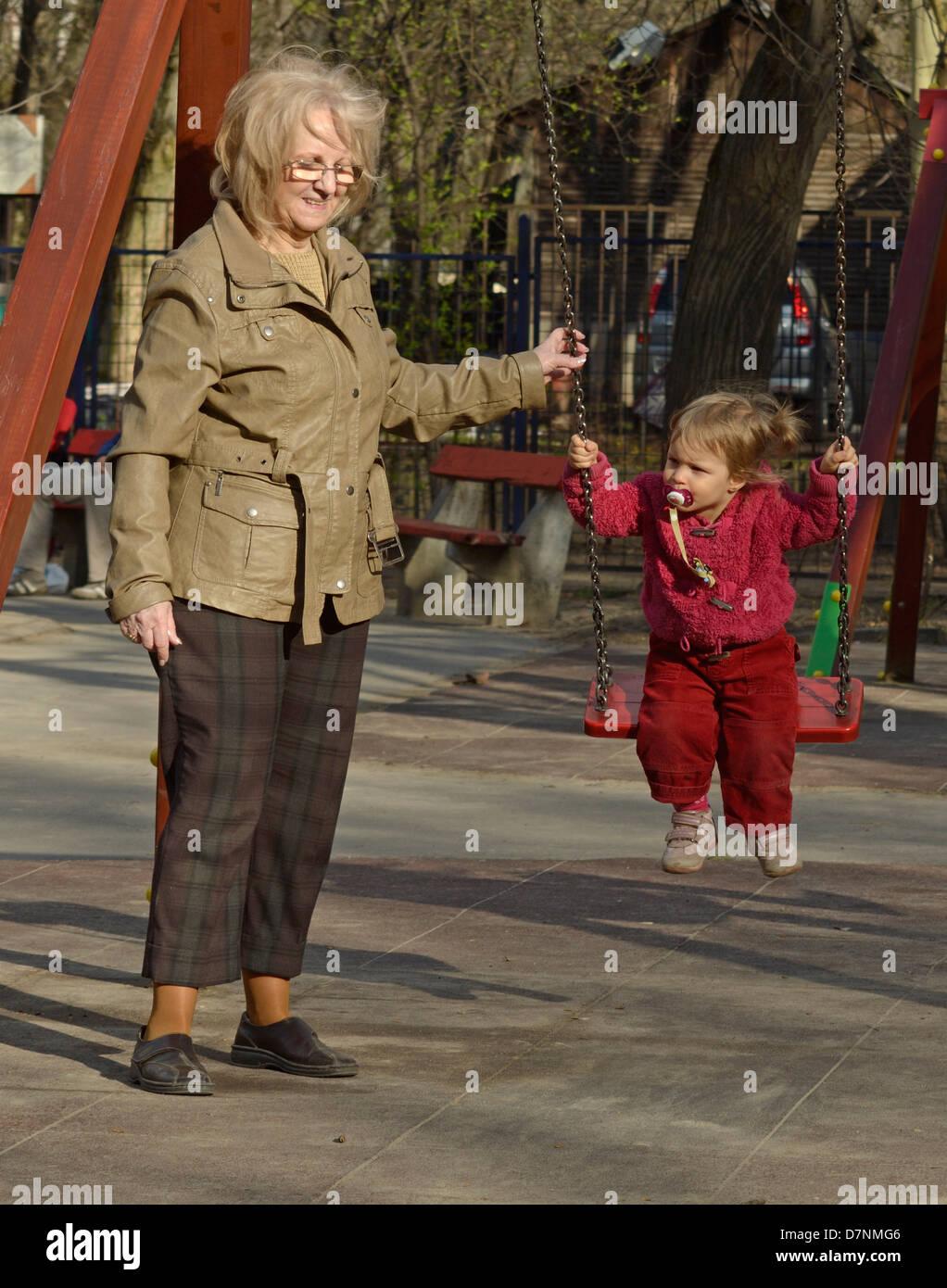 Generazioni della famiglia - Baby girl sullo swing con la Nonna presso il  parco giochi Immagini 7b61fb3362
