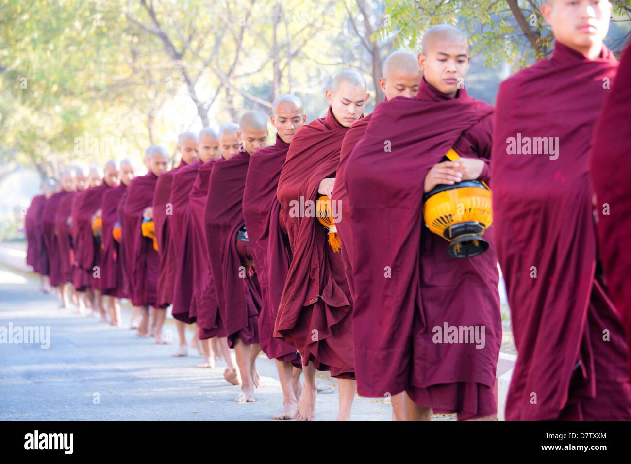 I monaci buddisti a piedi lungo la strada per raccogliere elemosine, nei pressi di Shwezigon Paya, Nyaung U, Bagan, Immagini Stock