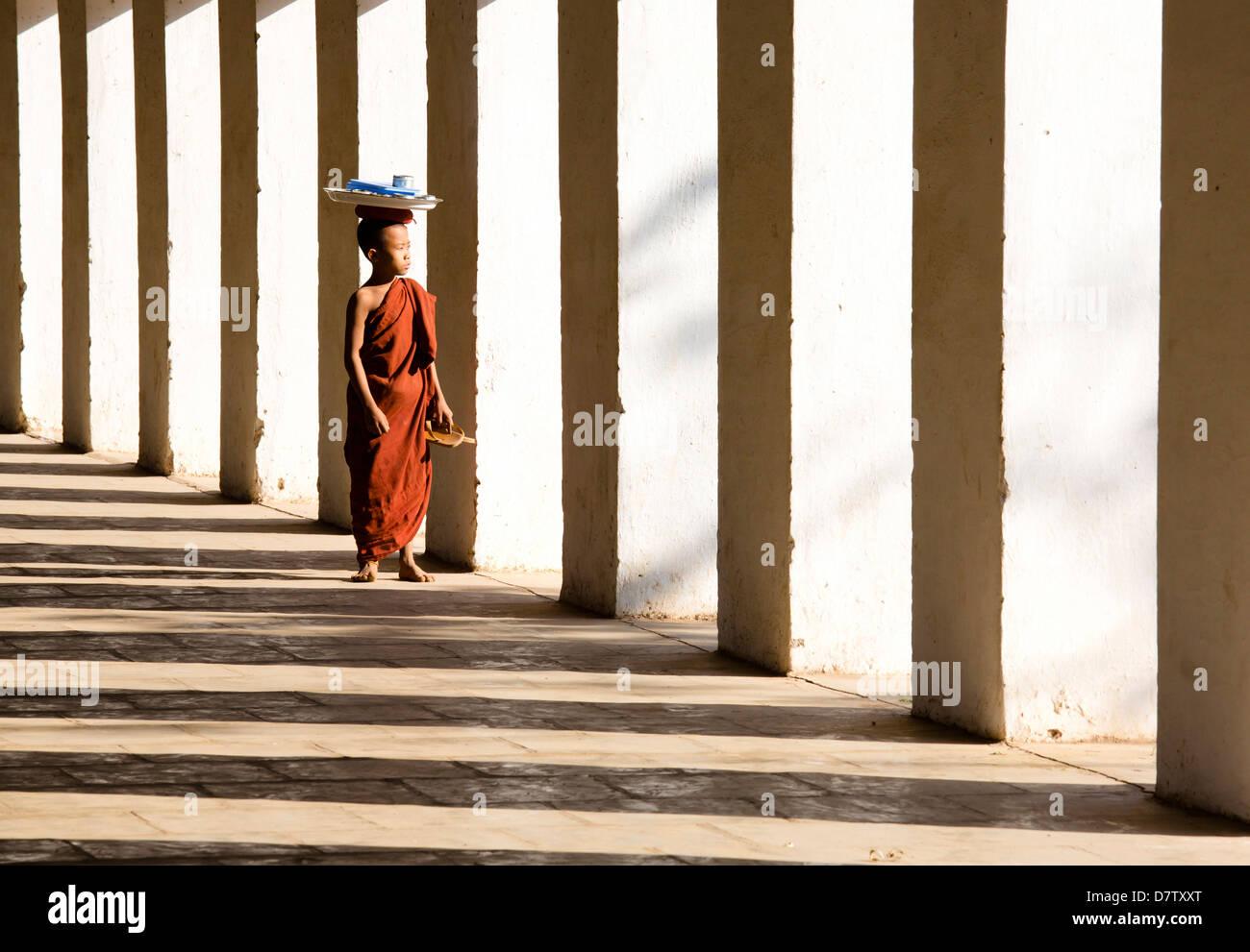 Il debuttante monaco buddista in piedi le ombre delle colonne a Shwezigon Paya, Nyaung U, Bagan, Birmania Immagini Stock