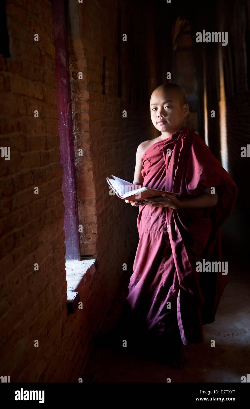 Il debuttante monaco buddista la lettura di scritture Buddhiste nella luce di una finestra in uno dei molti templi Immagini Stock