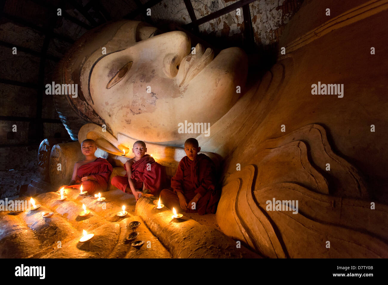Tre novizi monaci buddisti seduta da un grande Buddha reclinato alla luce delle candele, vicino Shwesandaw Paya, Immagini Stock