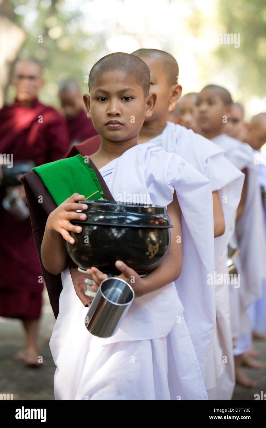 Il debuttante monache buddiste accodamento per un pasto presso il monastero Mahagandayon, Mandalay Birmania Immagini Stock