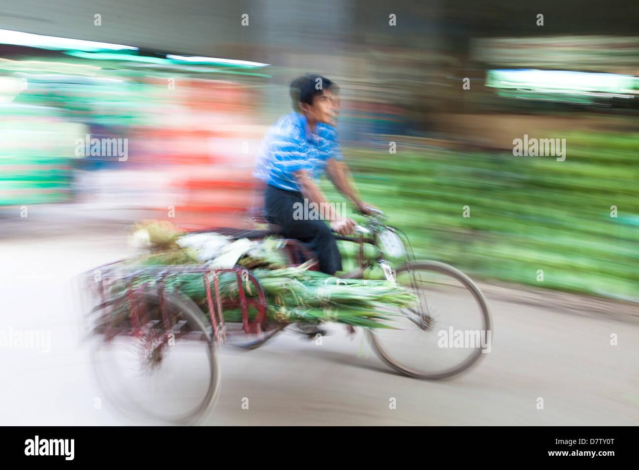 Panoramiche e immagine sfocata per aggiungere un senso di movimento di un uomo in bicicletta attraverso Thiri Mingalar Immagini Stock