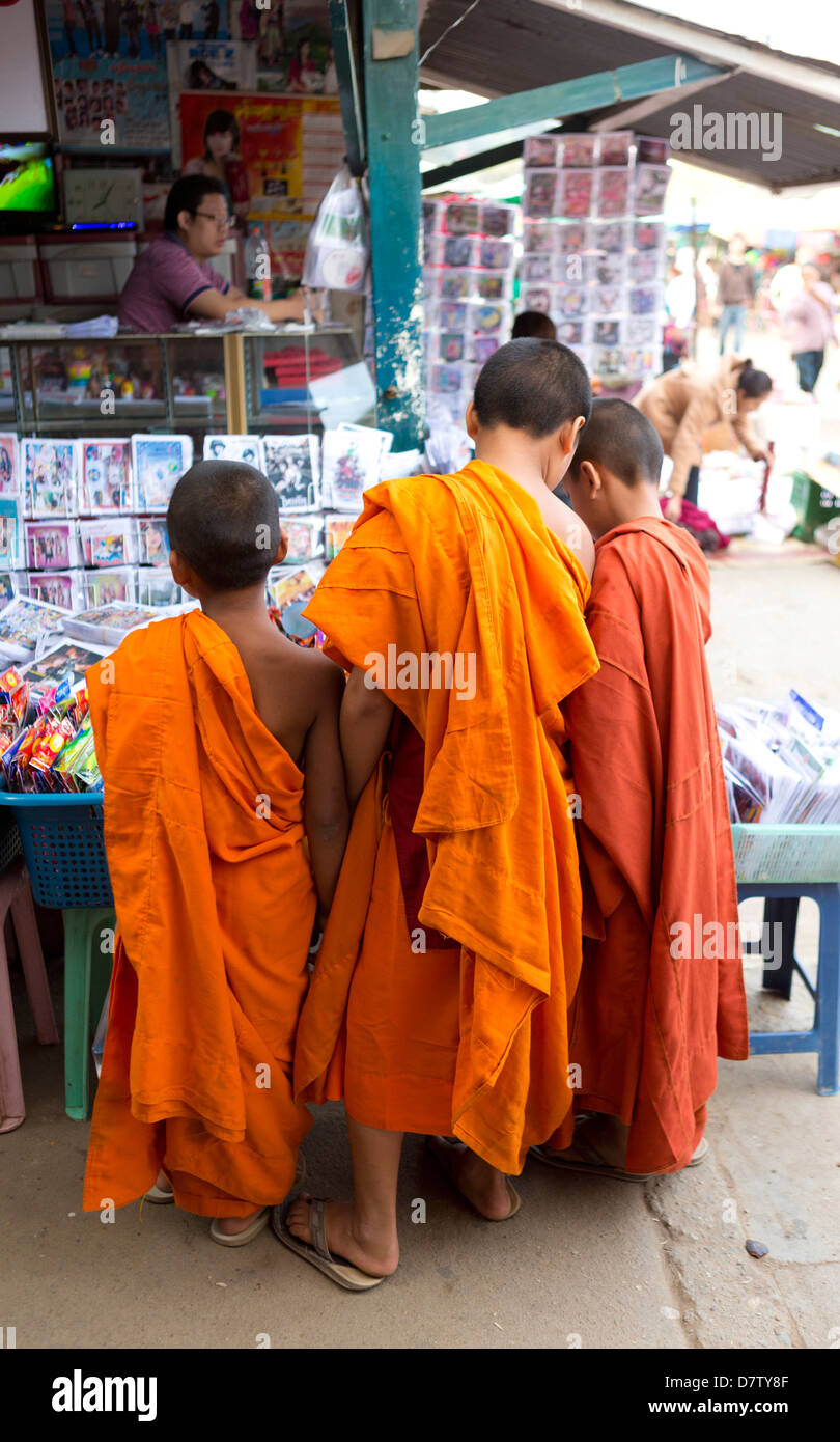 Tre monaci novizio comprare fumetti nel mercato del paese, Kengtung (Kyaingtong), Stato Shan, Birmania Immagini Stock