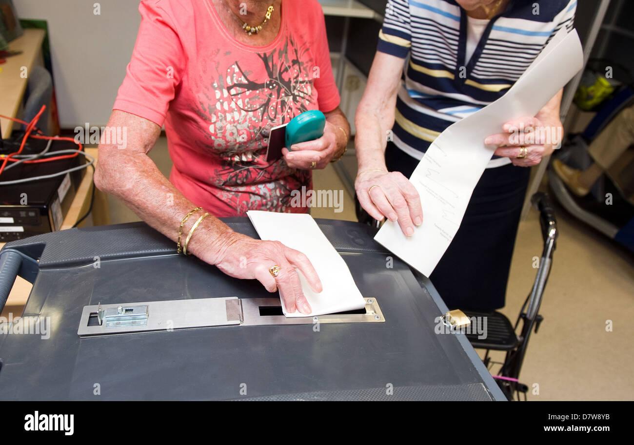 Due donna con loro schede elettorali sono gonna metterli in un urna Immagini Stock