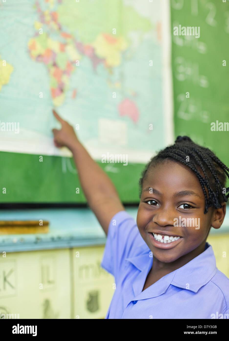 Studente utilizzando la mappa del mondo in classe Immagini Stock