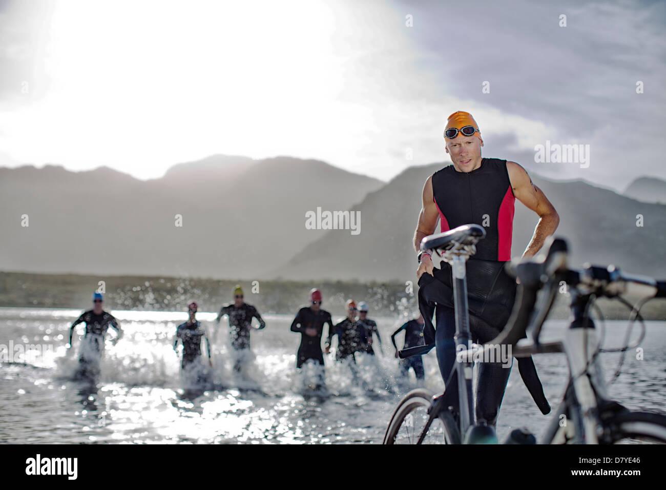 Triatleti emergenti dall'acqua Immagini Stock