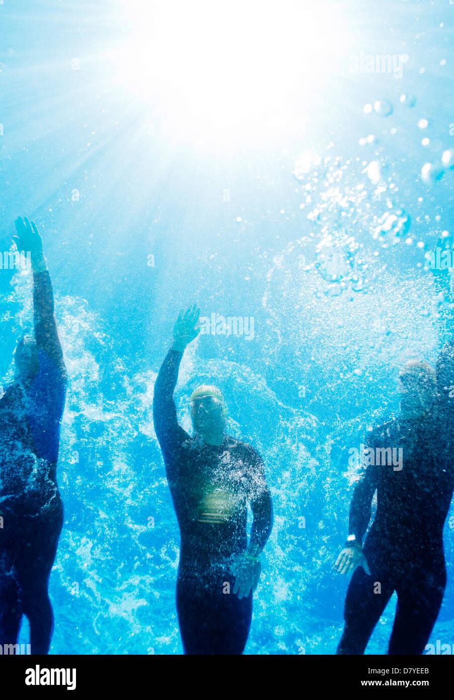 Triatleti nella muta subacquea Foto Stock