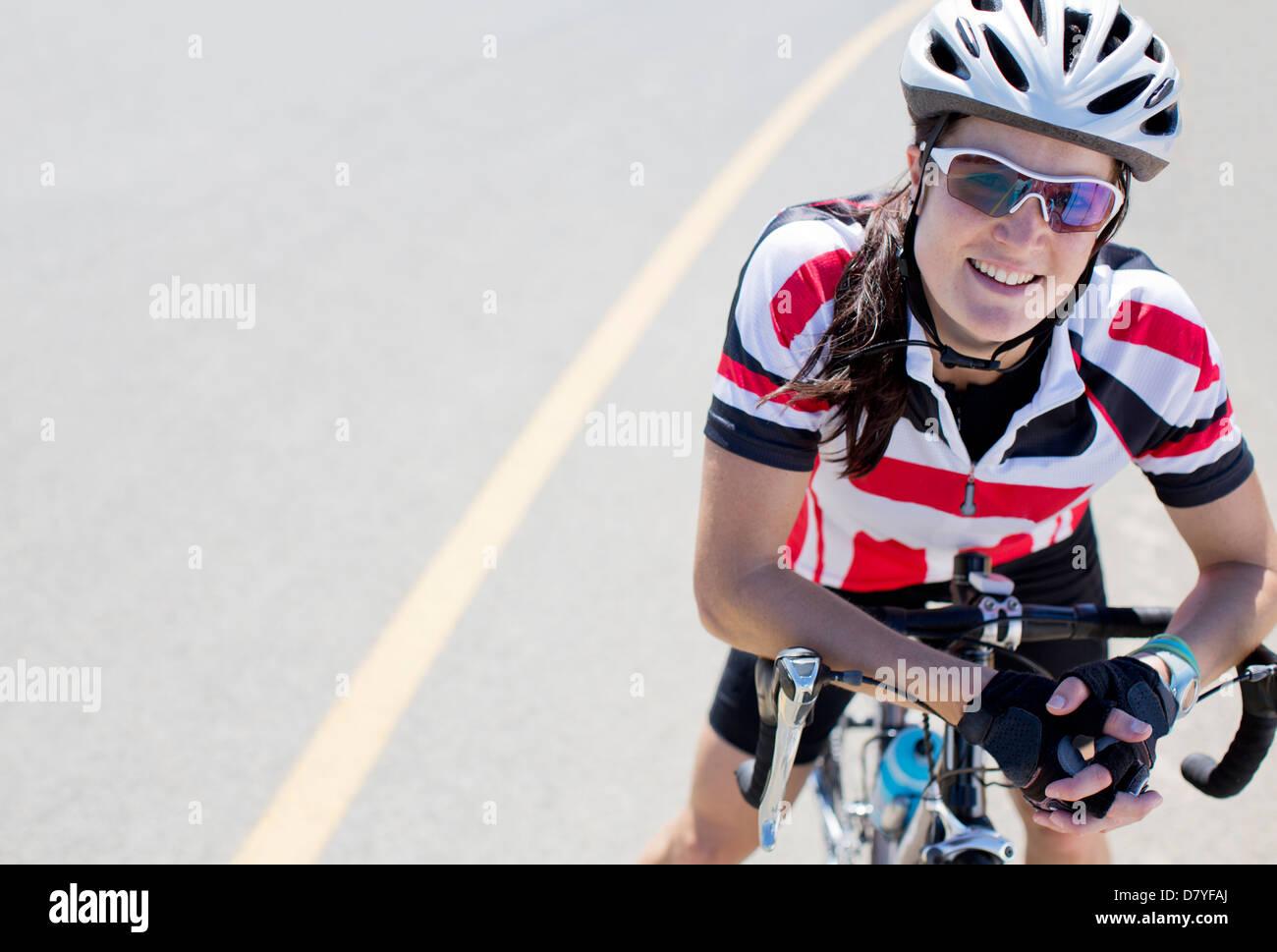 Ciclista sorridente sulla strada rurale Immagini Stock