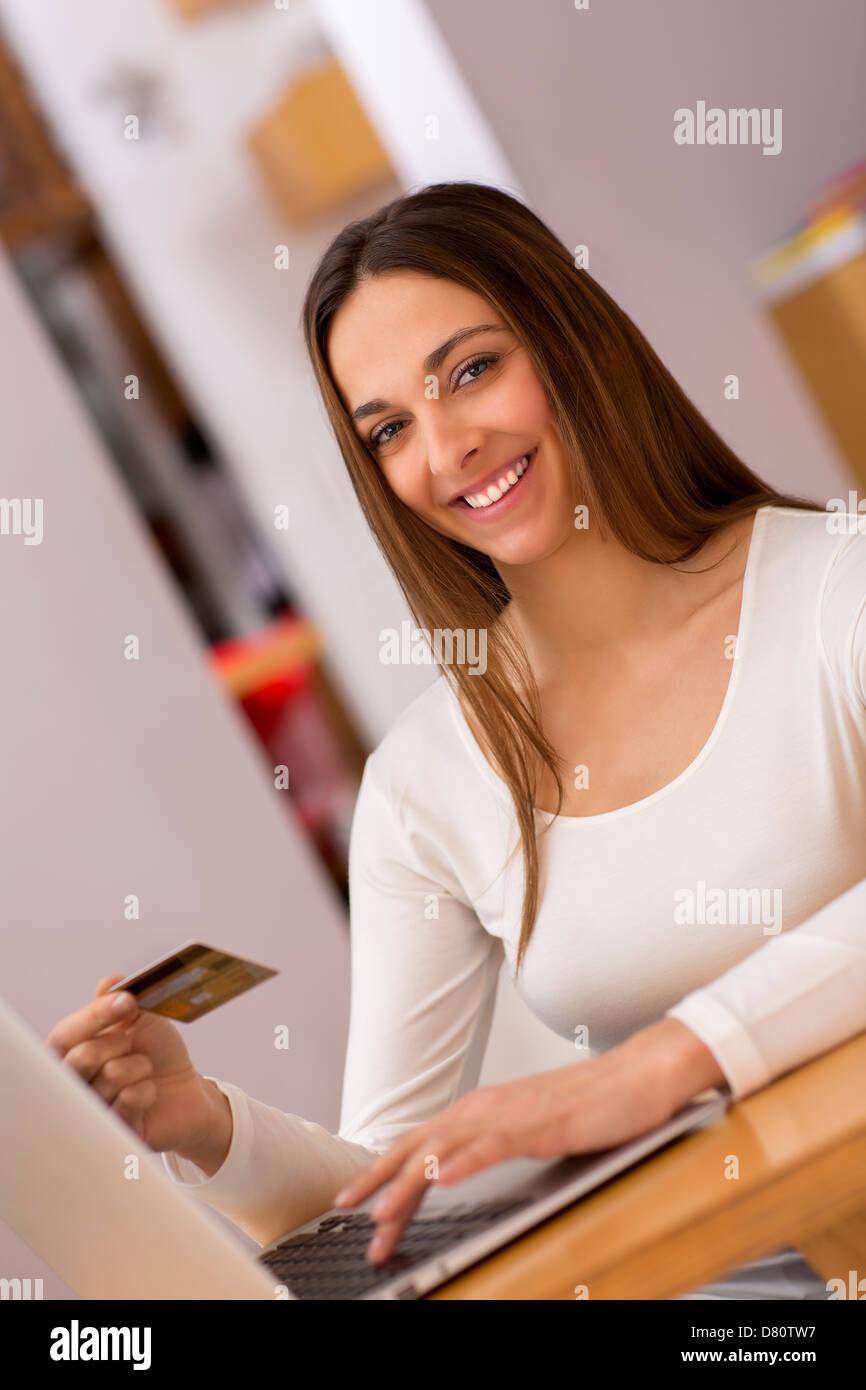 Donne in possesso di una carta di addebito e shopping dal web sul computer portatile Immagini Stock