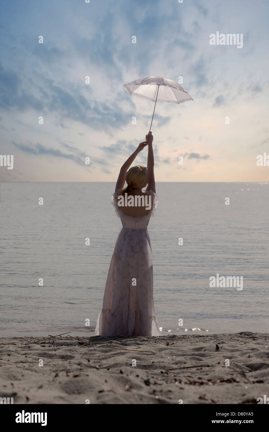 Una donna in spiaggia con un ombrellone bianco Immagini Stock