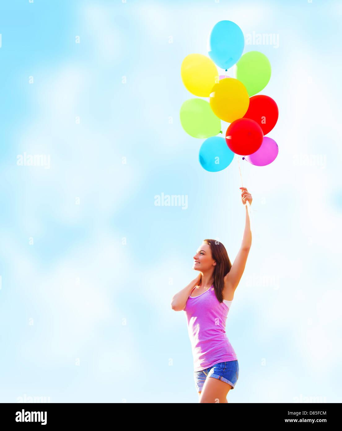 Bella giovane donna tenendo in mano molti palloncini colorati sul cielo azzurro sfondo, estate vacanze, concetto Immagini Stock