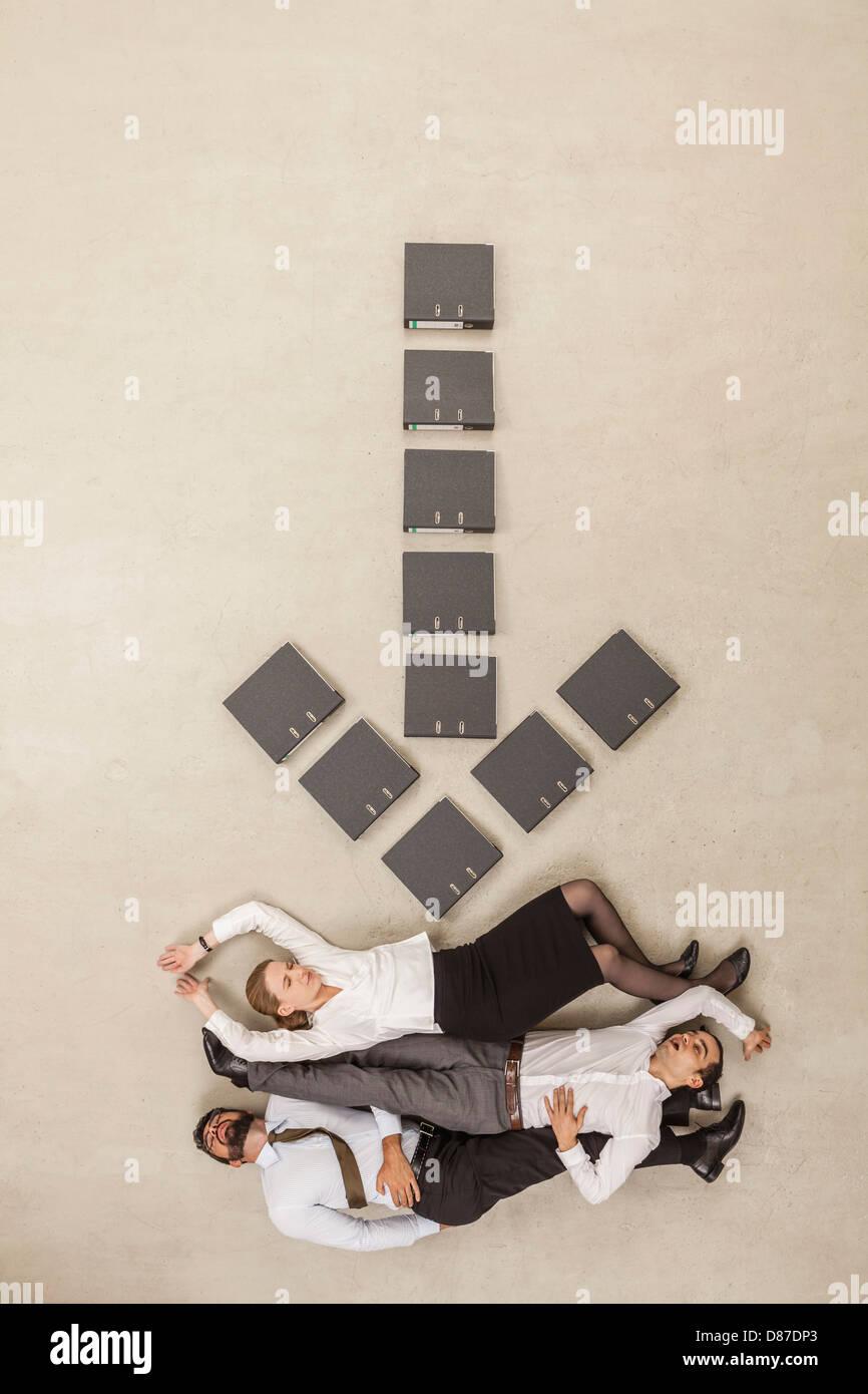 La gente di affari che giace sotto freccia giù segno formata da file Immagini Stock