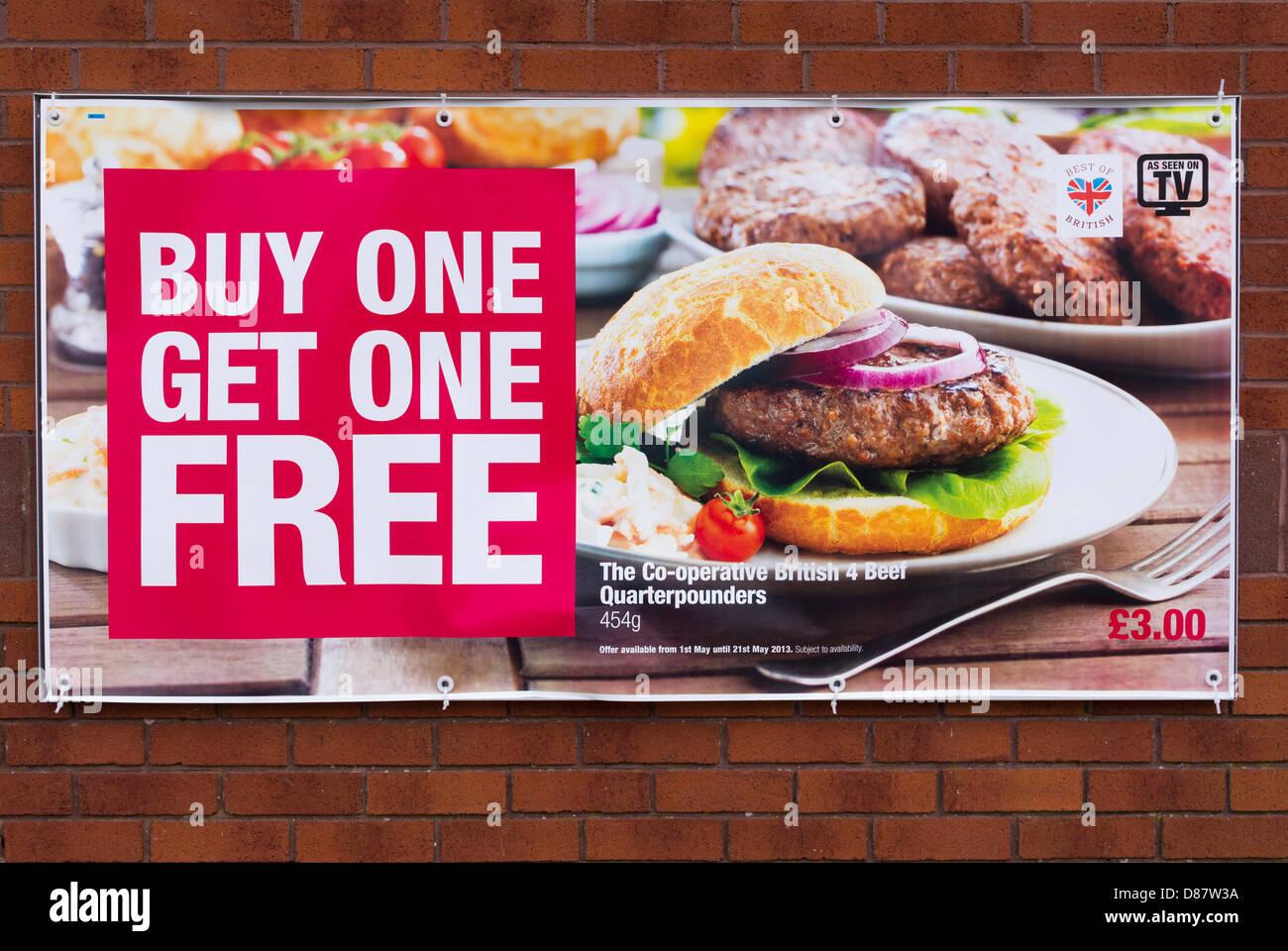 Paghi 1 e prendi 1 gratis cibo trattativa a buon mercato per gli hamburger su un cartellone su un co-op supermercato Immagini Stock