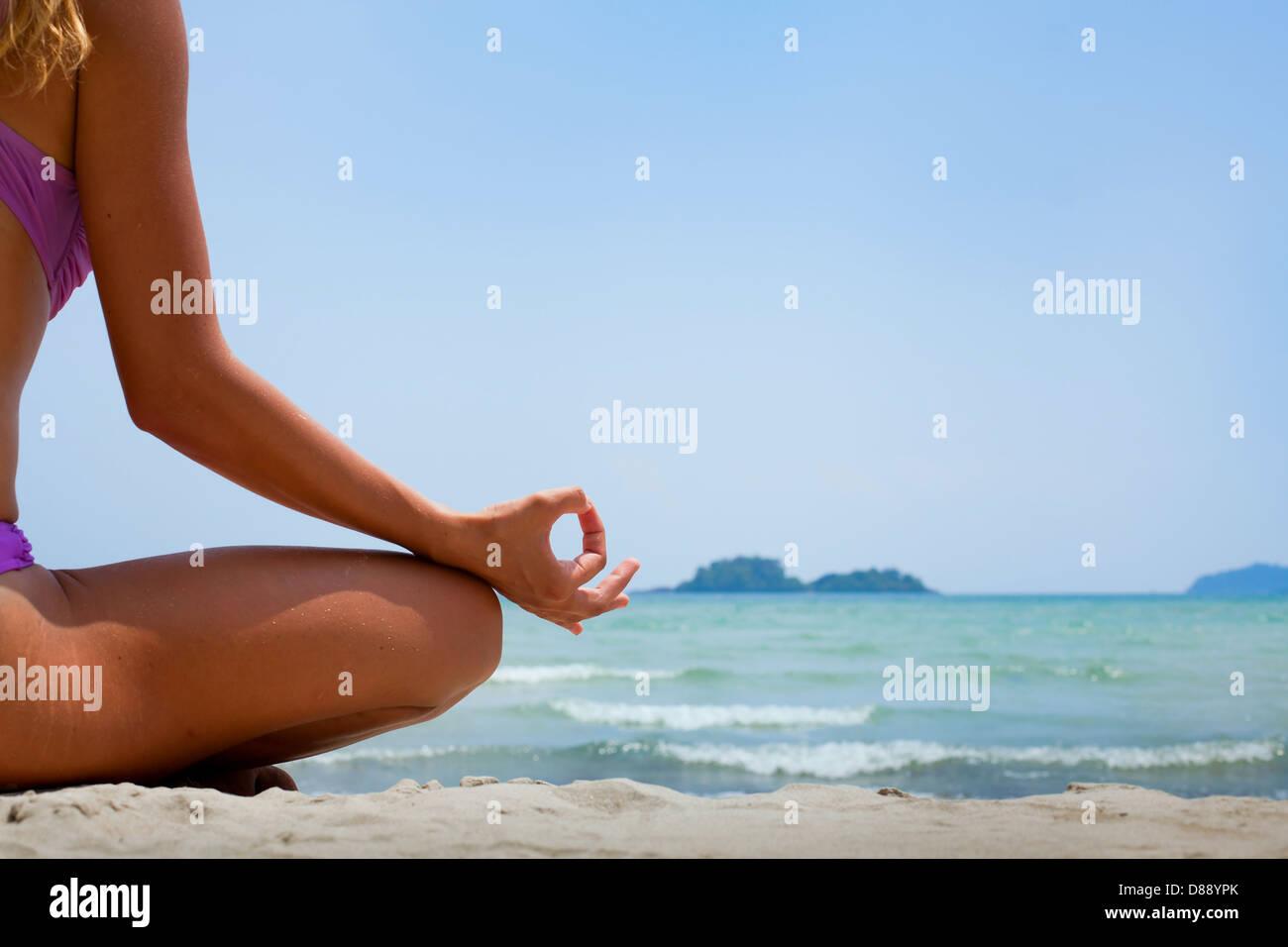 Sfondo di yoga, donna nella posizione del loto meditando sulla spiaggia Immagini Stock