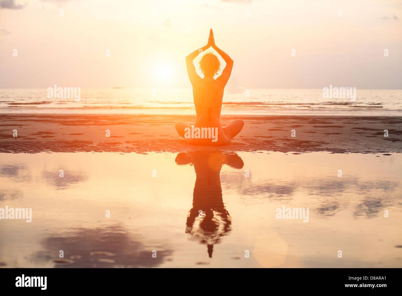 Yoga donna seduta in lotus pongono sulla spiaggia durante il tramonto, con riflessione in acqua (in luminosi colori) Immagini Stock