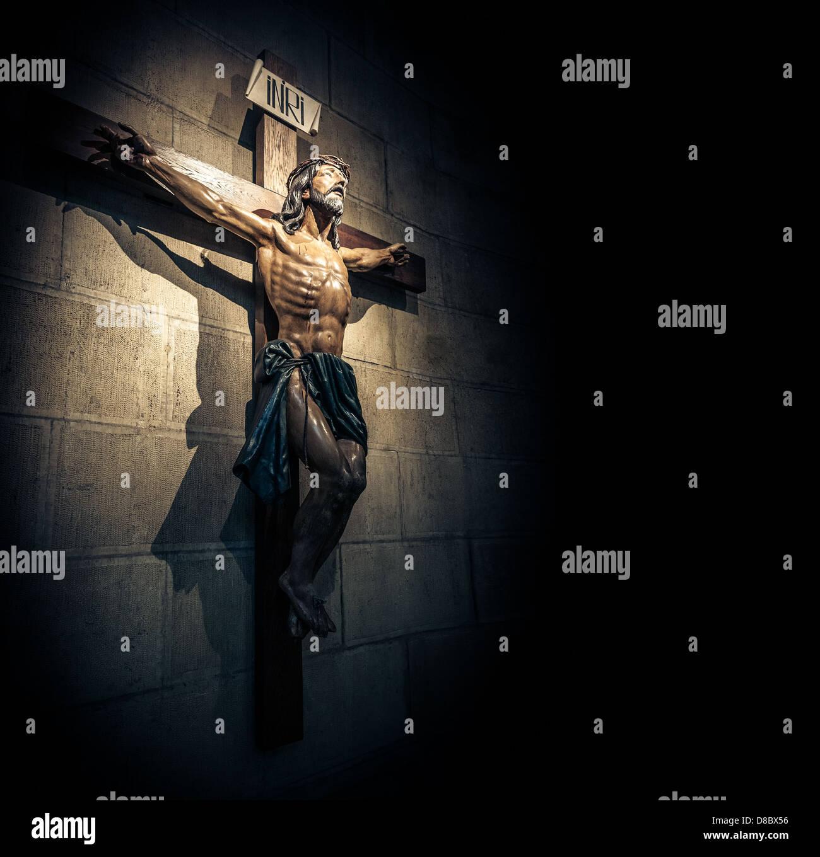 Crocifisso sulla parete in Spotlight all'interno della vecchia chiesa oscura o cattedrale. Gesù Cristo Immagini Stock