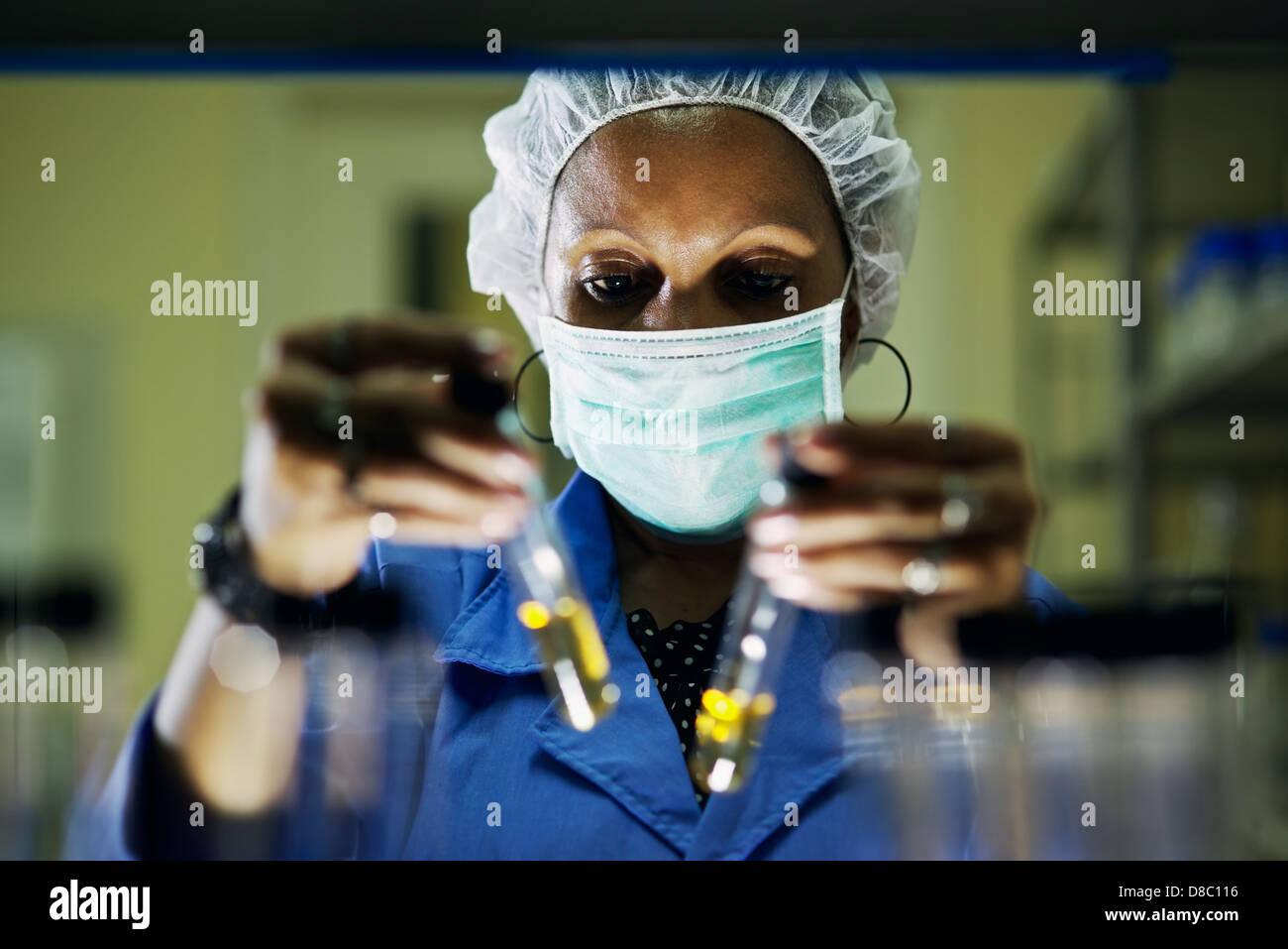La scienza e la ricerca, la donna lavora come farmacista guardando alla provetta di test in laboratorio Immagini Stock