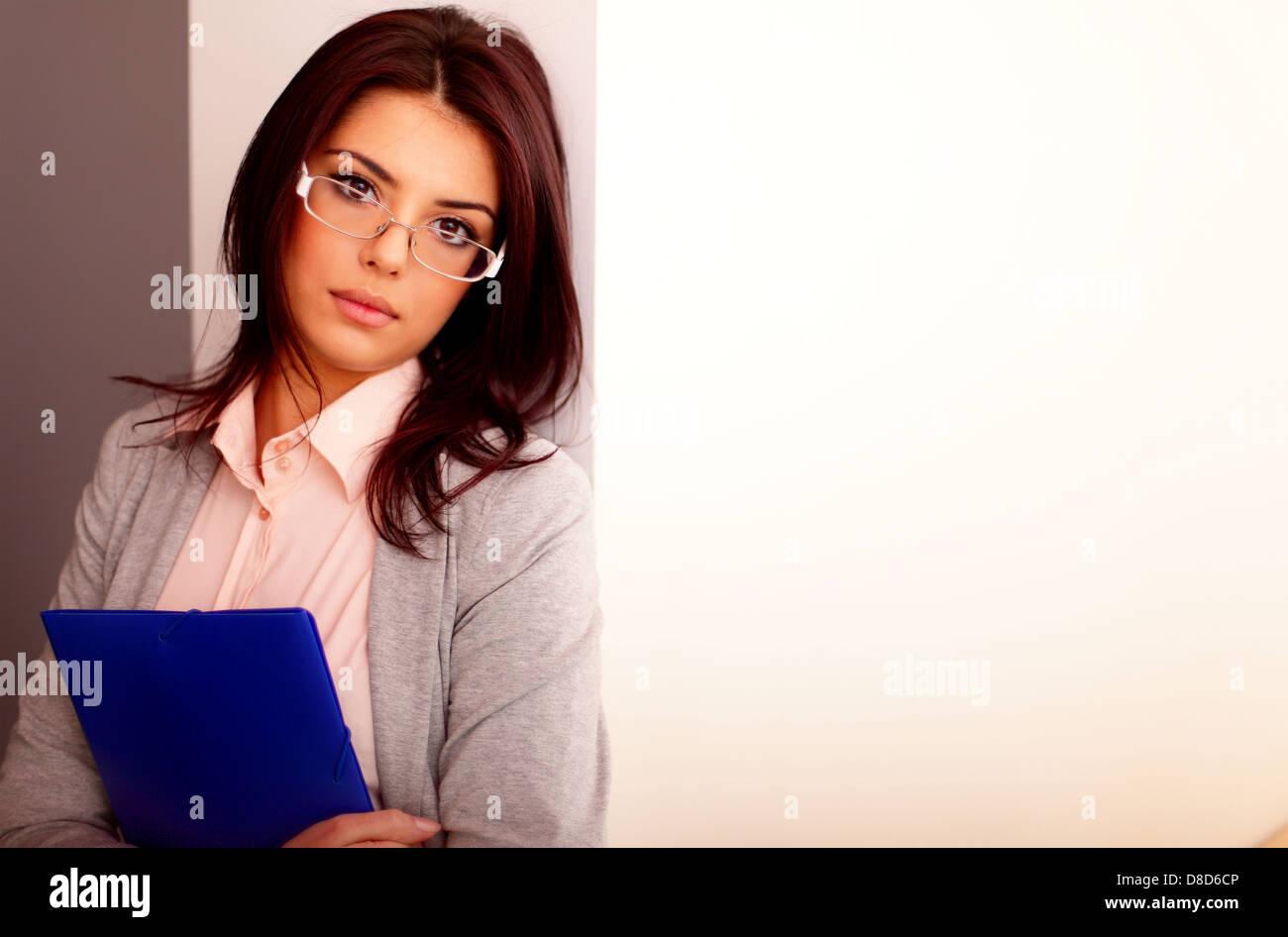 Bella giovane imprenditrice in office tenendo una cartella Immagini Stock
