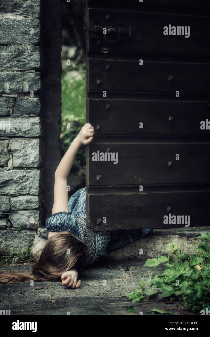 Una giovane ragazza distesa sul terreno in prossimità di una vecchia porta, cercando di ottenere il massimo Immagini Stock
