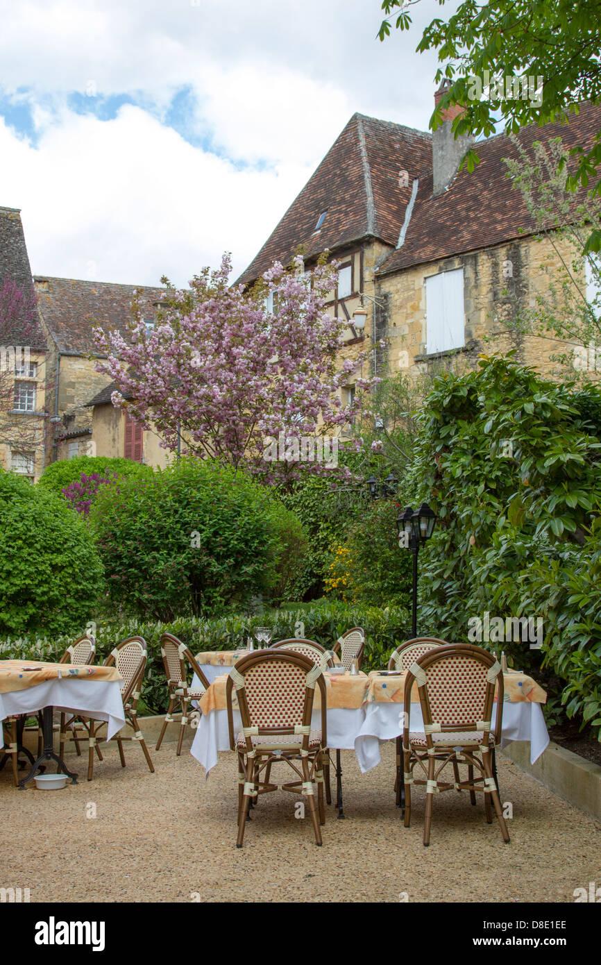 Cortile esterno a pranzare in un ristorante dal medievale edifici di pietra arenaria di affascinante Sarlat Dordogne Immagini Stock