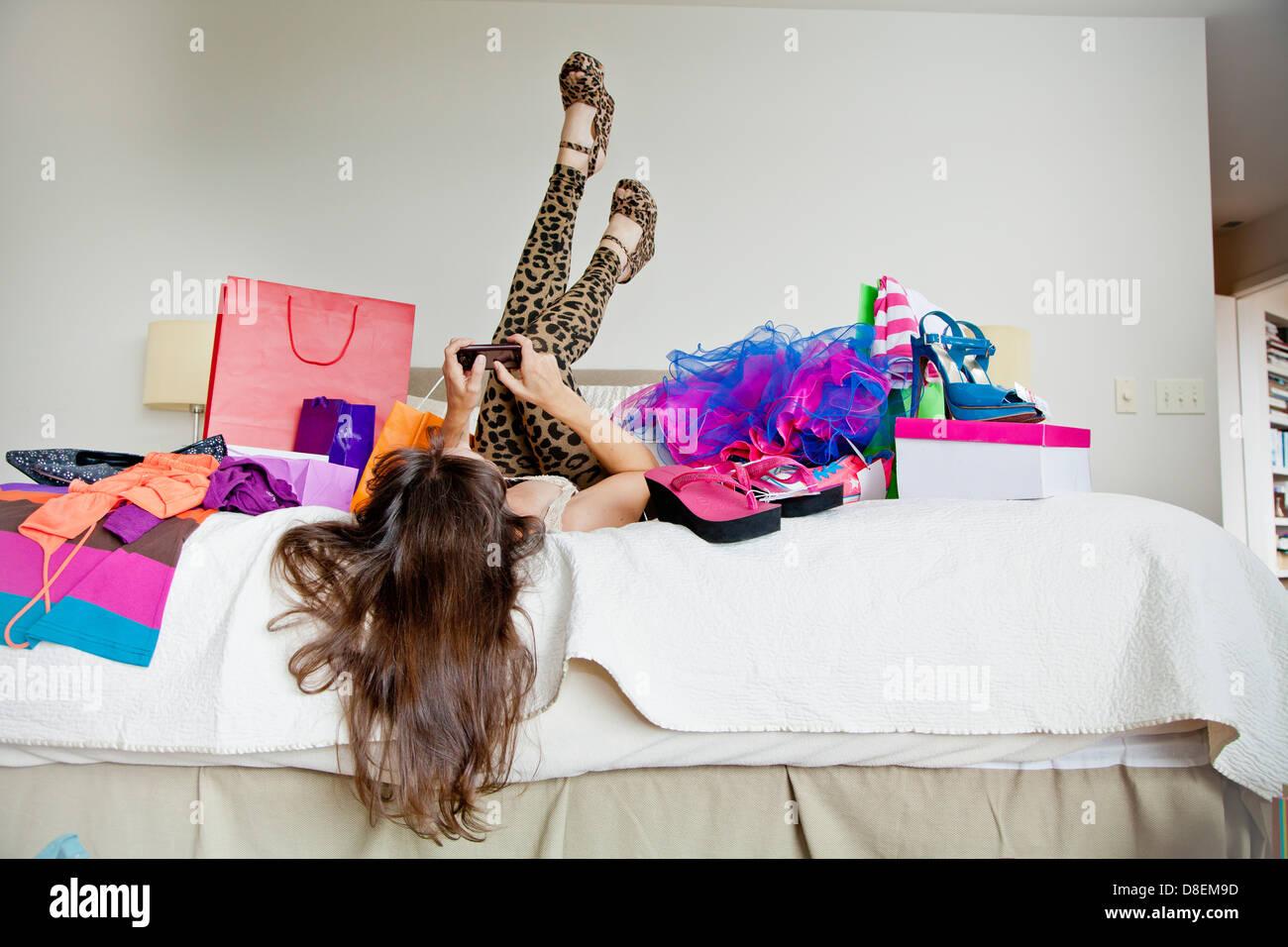 Donna sul letto circondato da borse per lo shopping Foto Stock