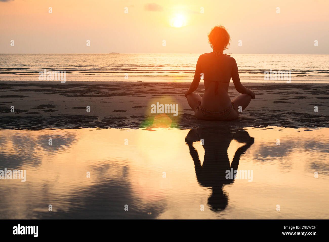 Yoga donna seduta in lotus pongono sulla spiaggia durante il tramonto, con riflessione in acqua - in colori luminosi. Immagini Stock