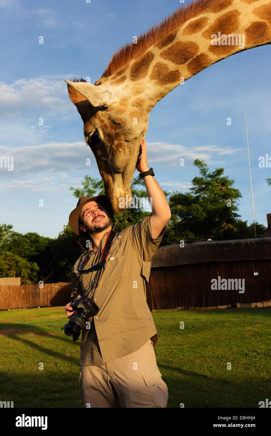 Uomo di fotografare la giraffa.Modello rilasciato Immagini Stock