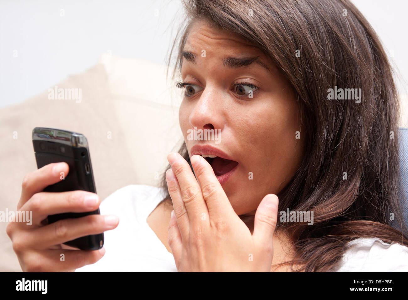 Giovane donna con espressione di shock guardando lei i-phone Immagini Stock