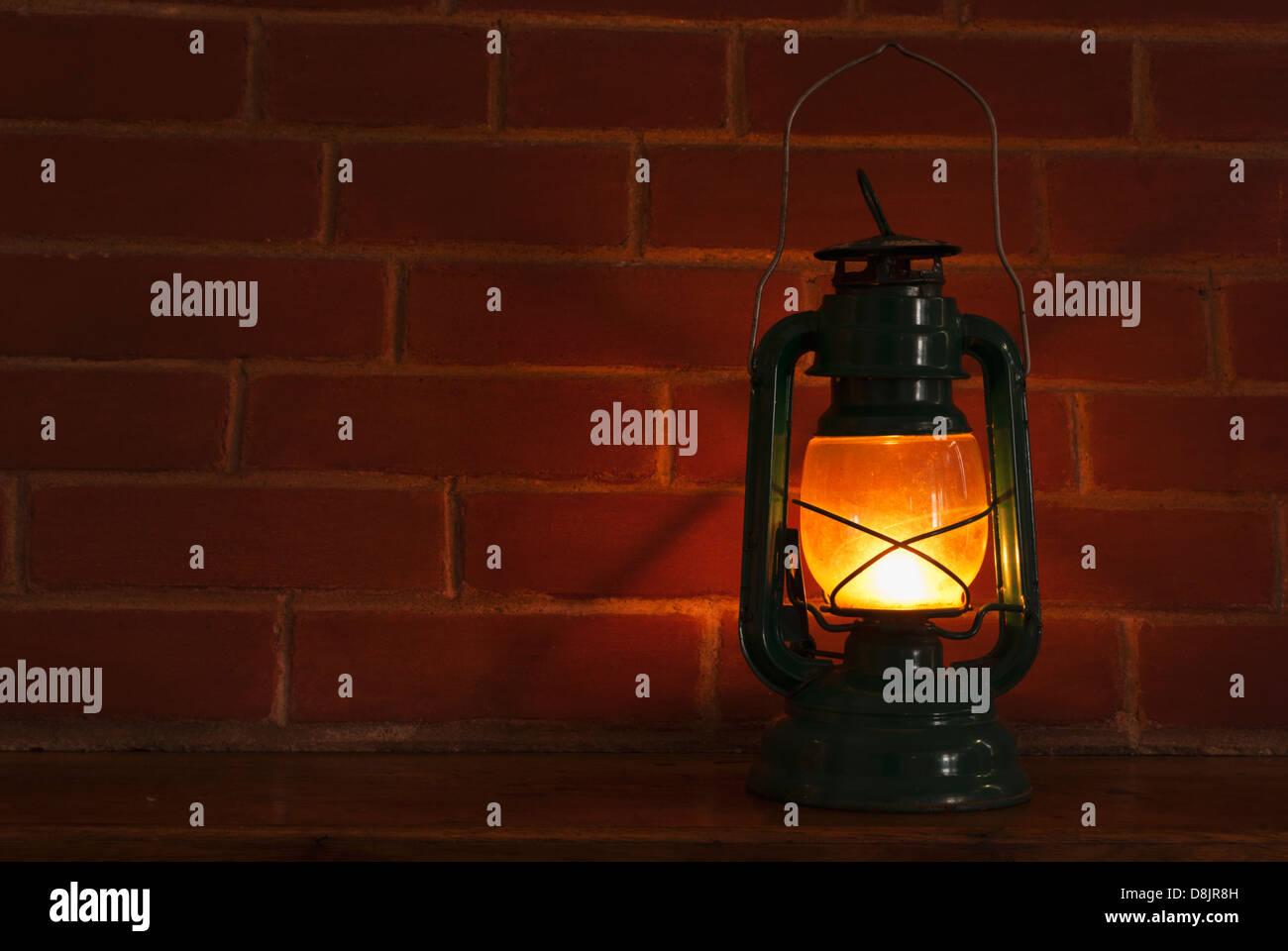 Una lampada ad olio lanterna illuminazione di stile nella parte anteriore di un brickwall sfondo. Immagini Stock