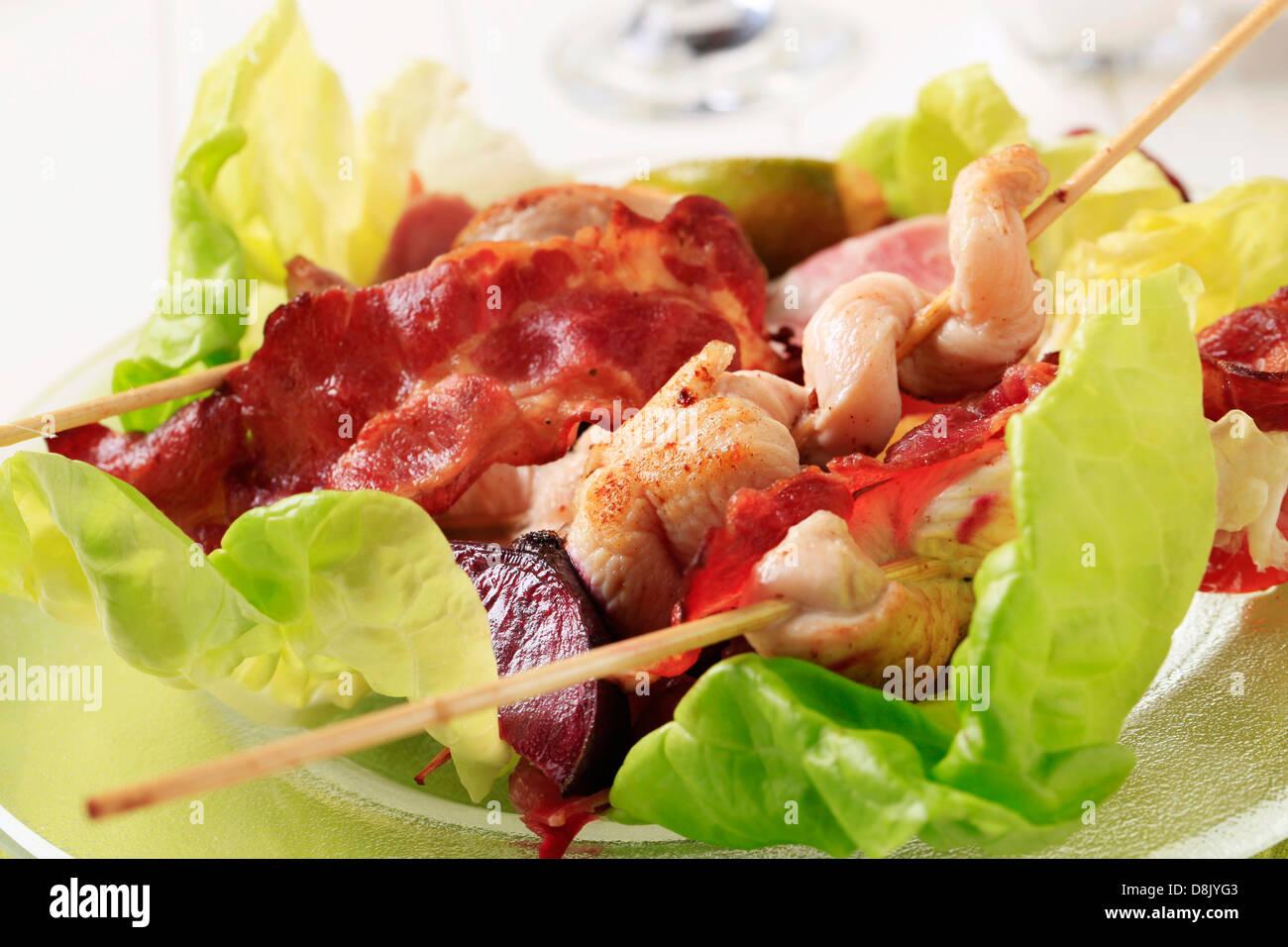 Spiedini di pollo e le strisce di pancetta servita su foglie di lattuga Immagini Stock