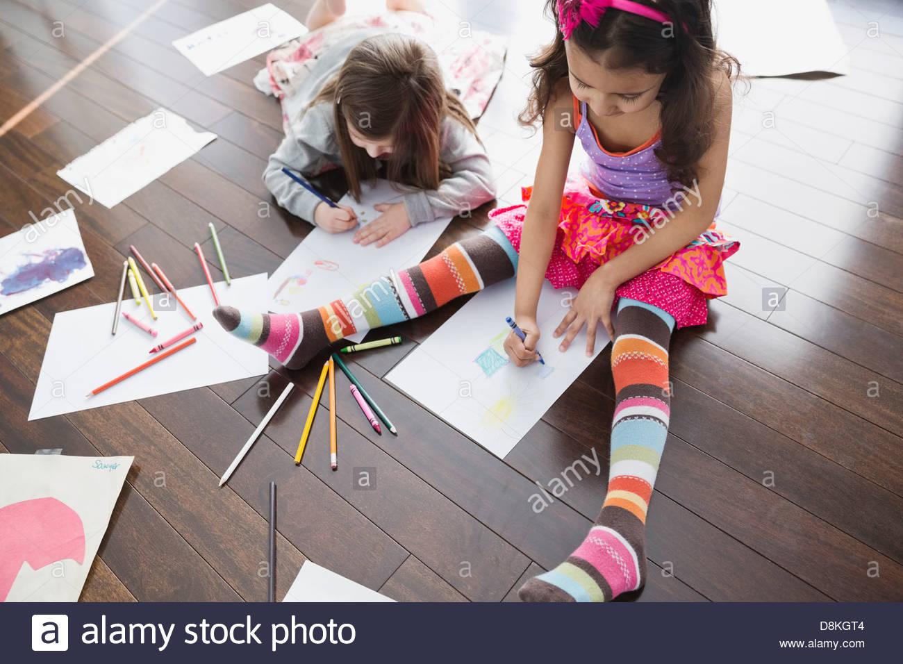 Angolo di Alta Vista della colorazione delle ragazze a casa Immagini Stock