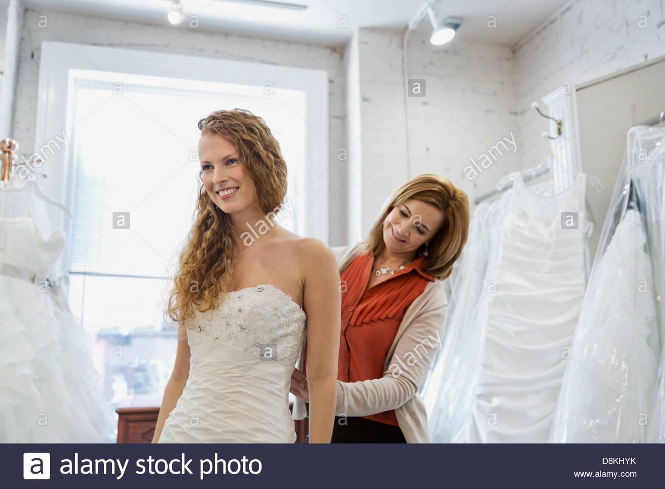 Donna cercando in abito da sposa con la madre al negozio nuziale Immagini Stock