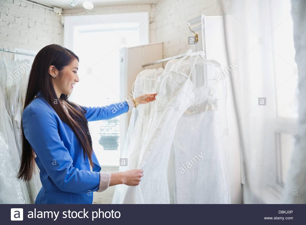 Giovane donna scelta abito da sposa in negozio nuziale Immagini Stock