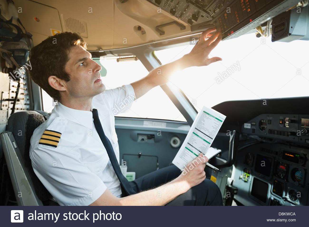 Maschio di controllo pilota sul pannello di comando nella cabina di pilotaggio aereo Immagini Stock