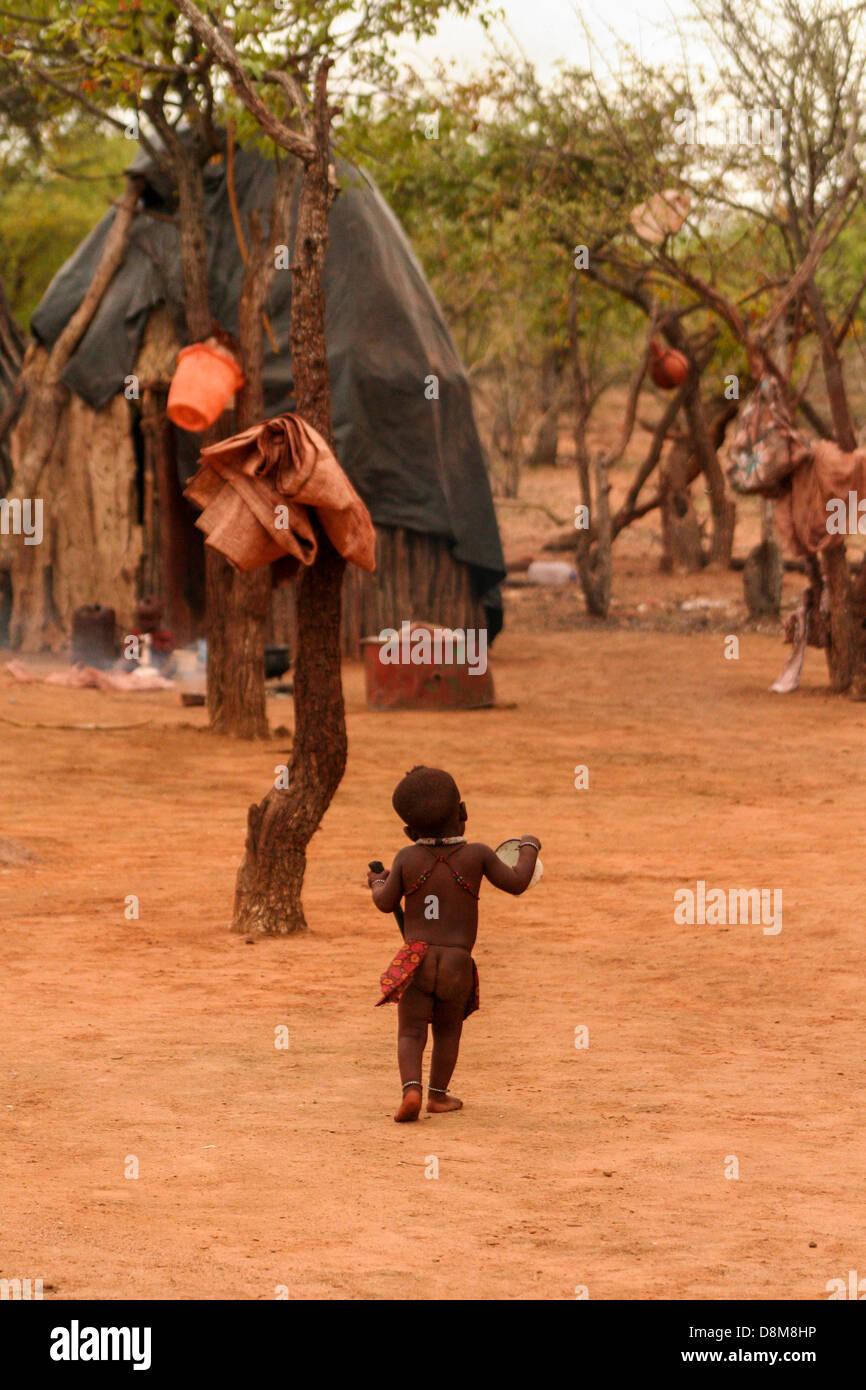 Un bambino a piedi attorno al loro villaggio Himba. Immagini Stock