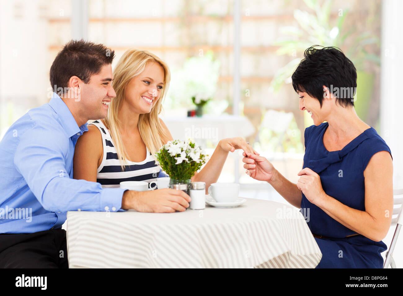 Felice giovane donna con il fidanzato che mostra il suo anello di fidanzamento a sua madre Immagini Stock