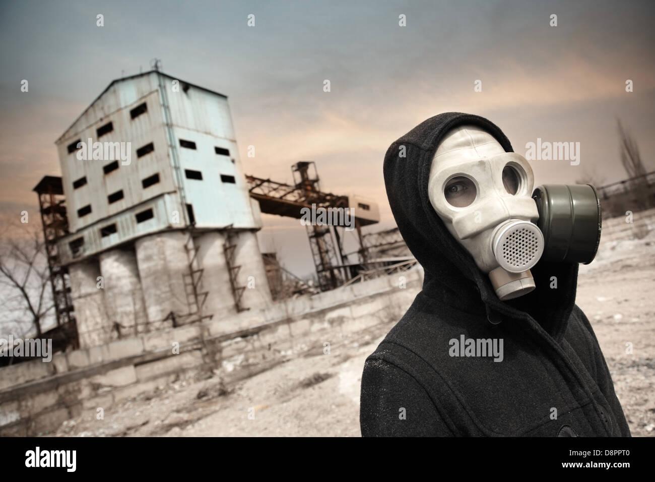 Umano nella maschera a gas all'aperto e fabbrica industriale su uno sfondo Foto Stock
