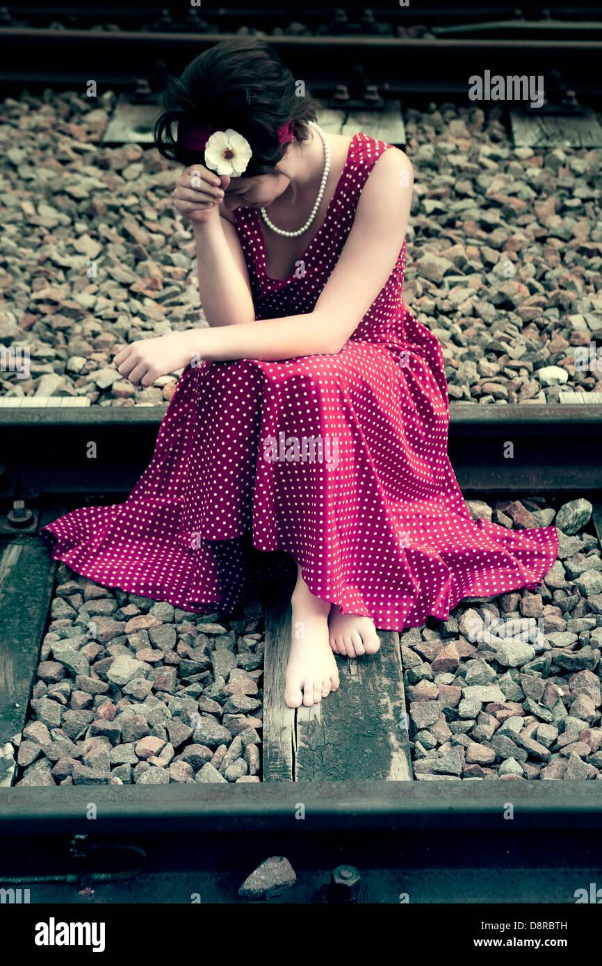 Una ragazza triste su binari ferroviari Immagini Stock