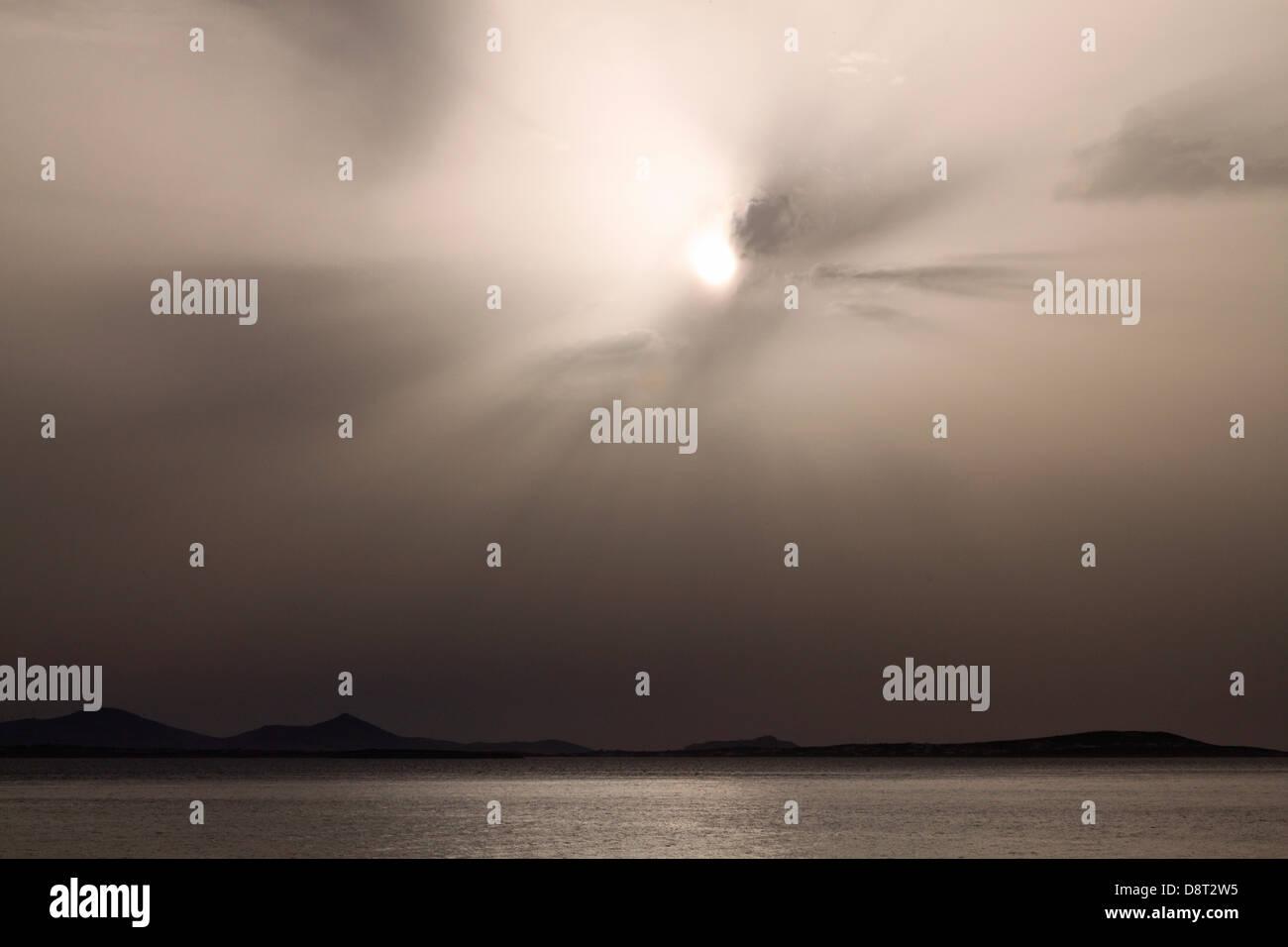 Cielo tempestoso sopra l'oceano con sun nasconde nelle nuvole scure Immagini Stock