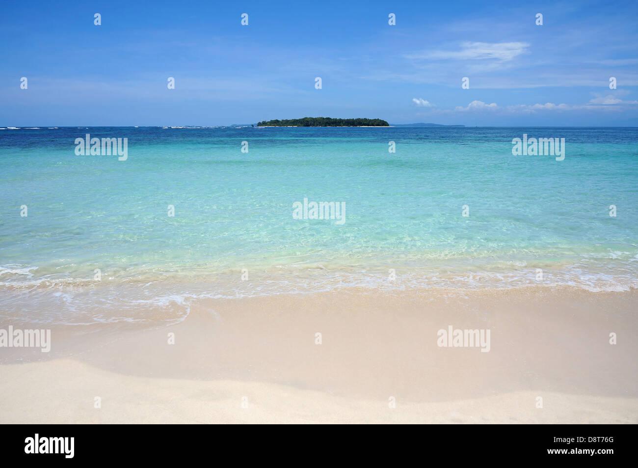 Spiaggia sabbiosa tropicale shore con acqua turchese e un'isola all'orizzonte, il mare dei Caraibi Immagini Stock