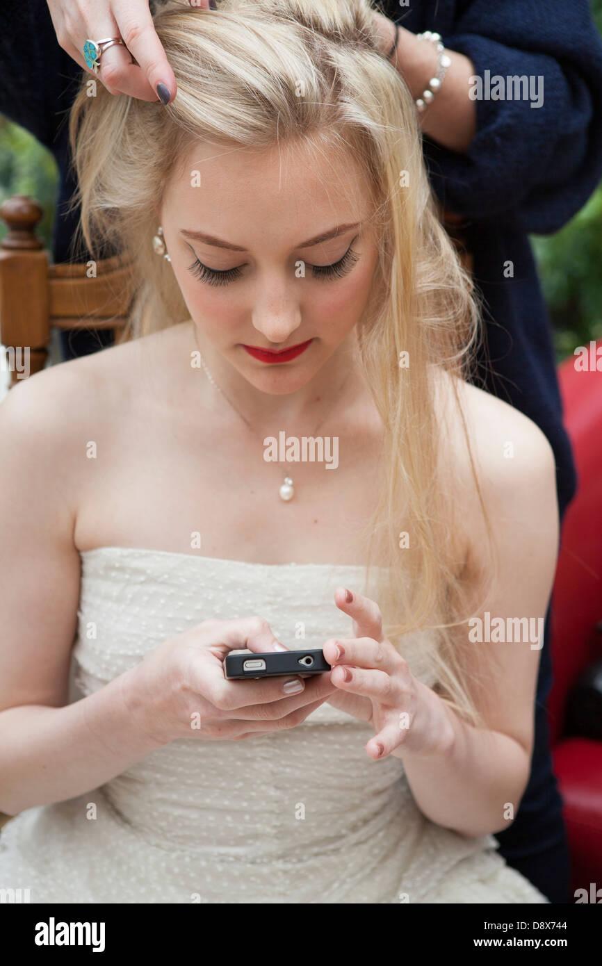Sposa texting ,durante il make-up Immagini Stock