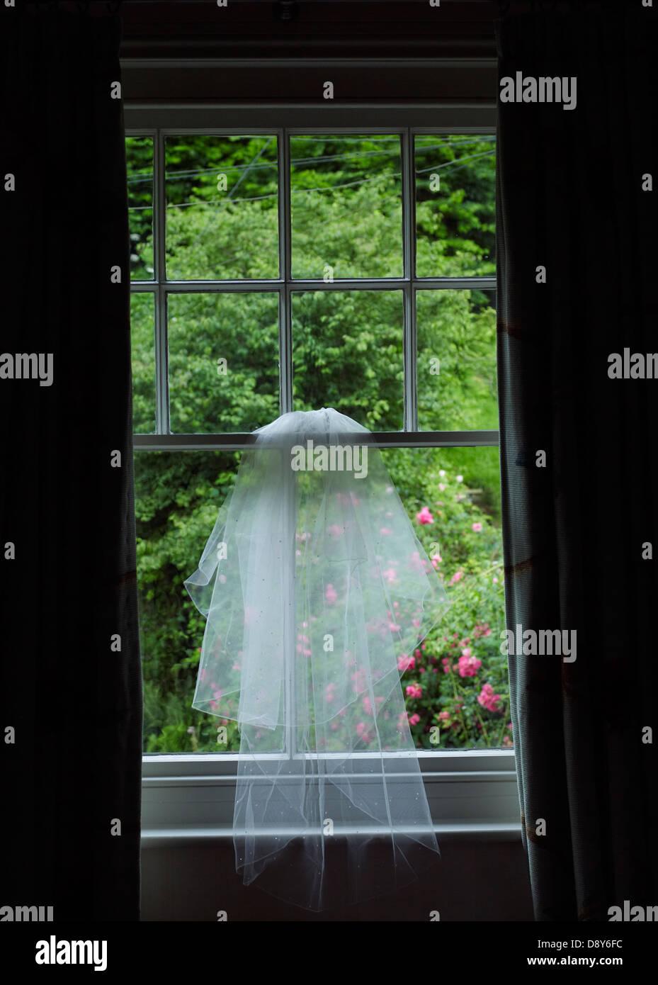 Un velo di nozze appeso ad una finestra che si affaccia su un giardino verde. Immagini Stock