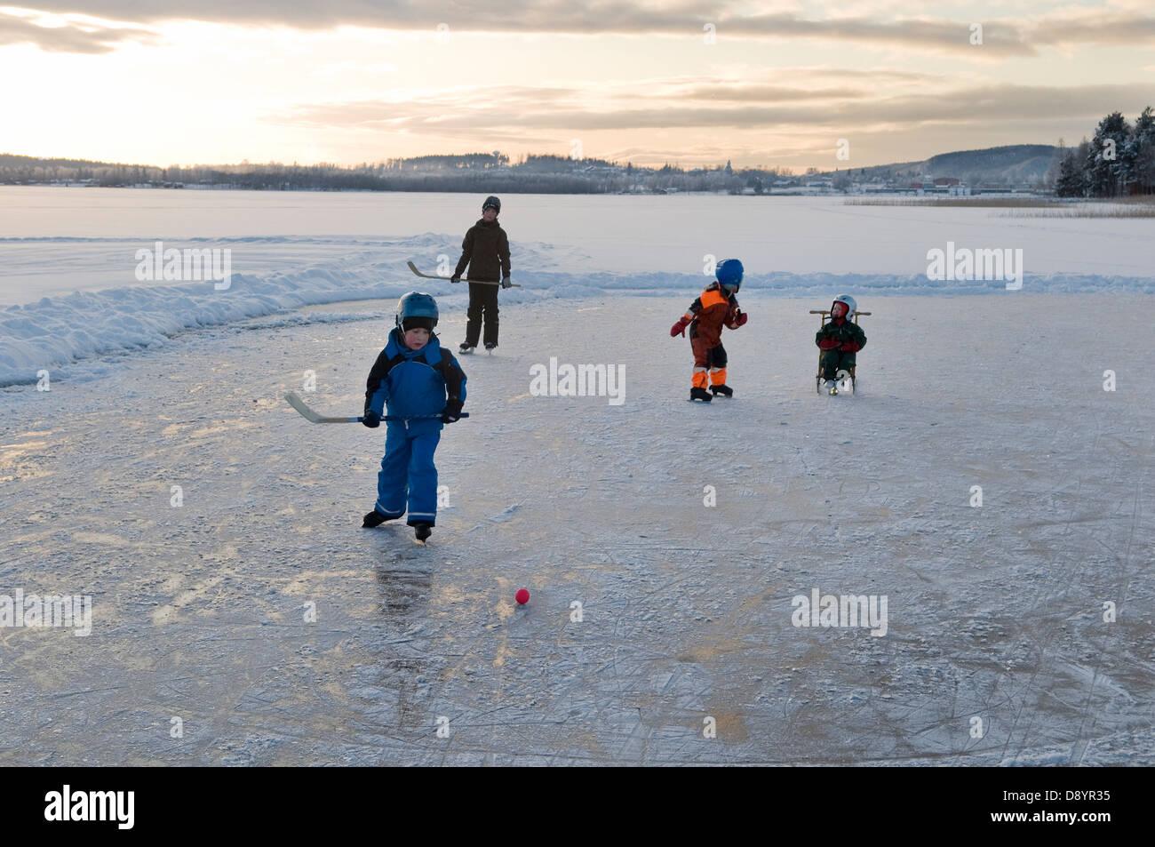 Bambini che giocano hockey su ghiaccio sul lago ghiacciato Immagini Stock