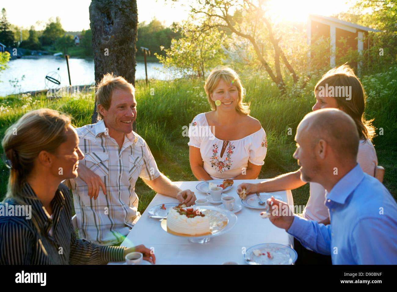Cinque amici haveing una torta, Fejan, arcipelago di Stoccolma, Svezia. Foto Stock
