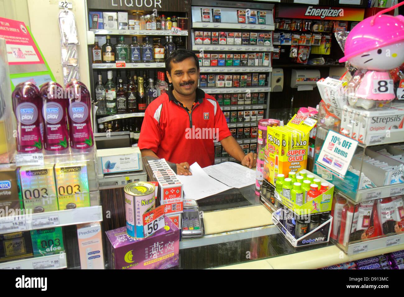 Singapore Kallang Road a 7-Eleven convenience store uomo asiatico lavoro cassiere uniforme del contatore all'interno Immagini Stock